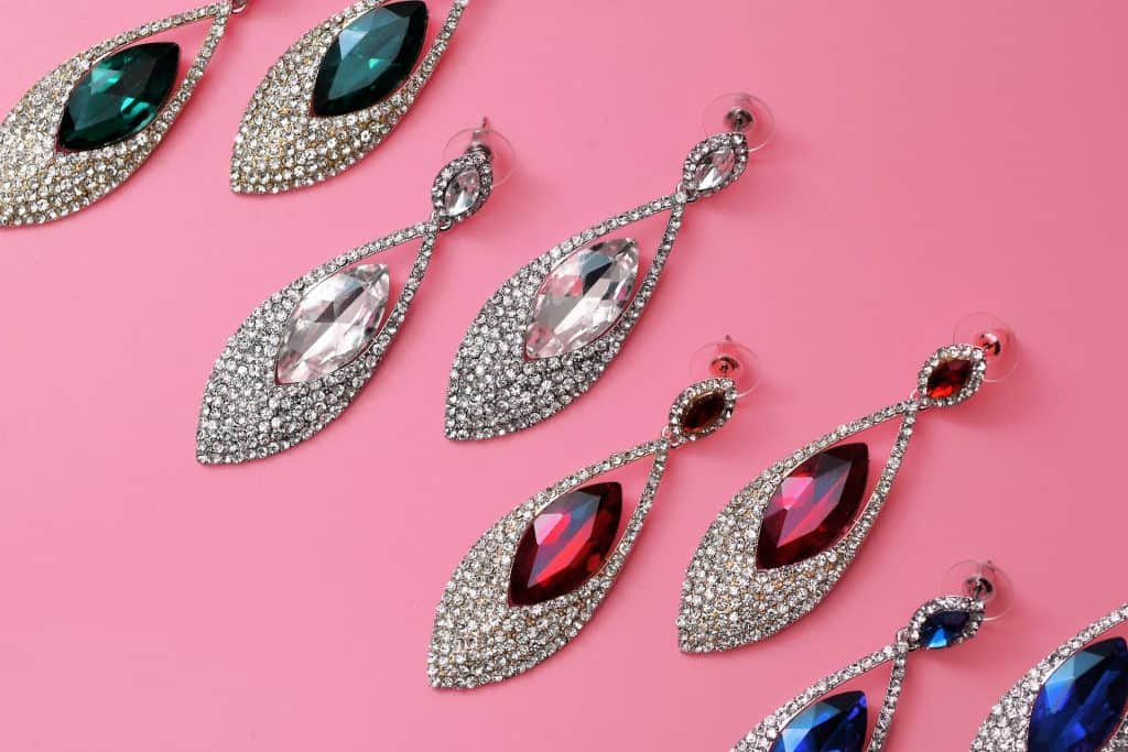 Pairs of jewelled earrings on a pink background